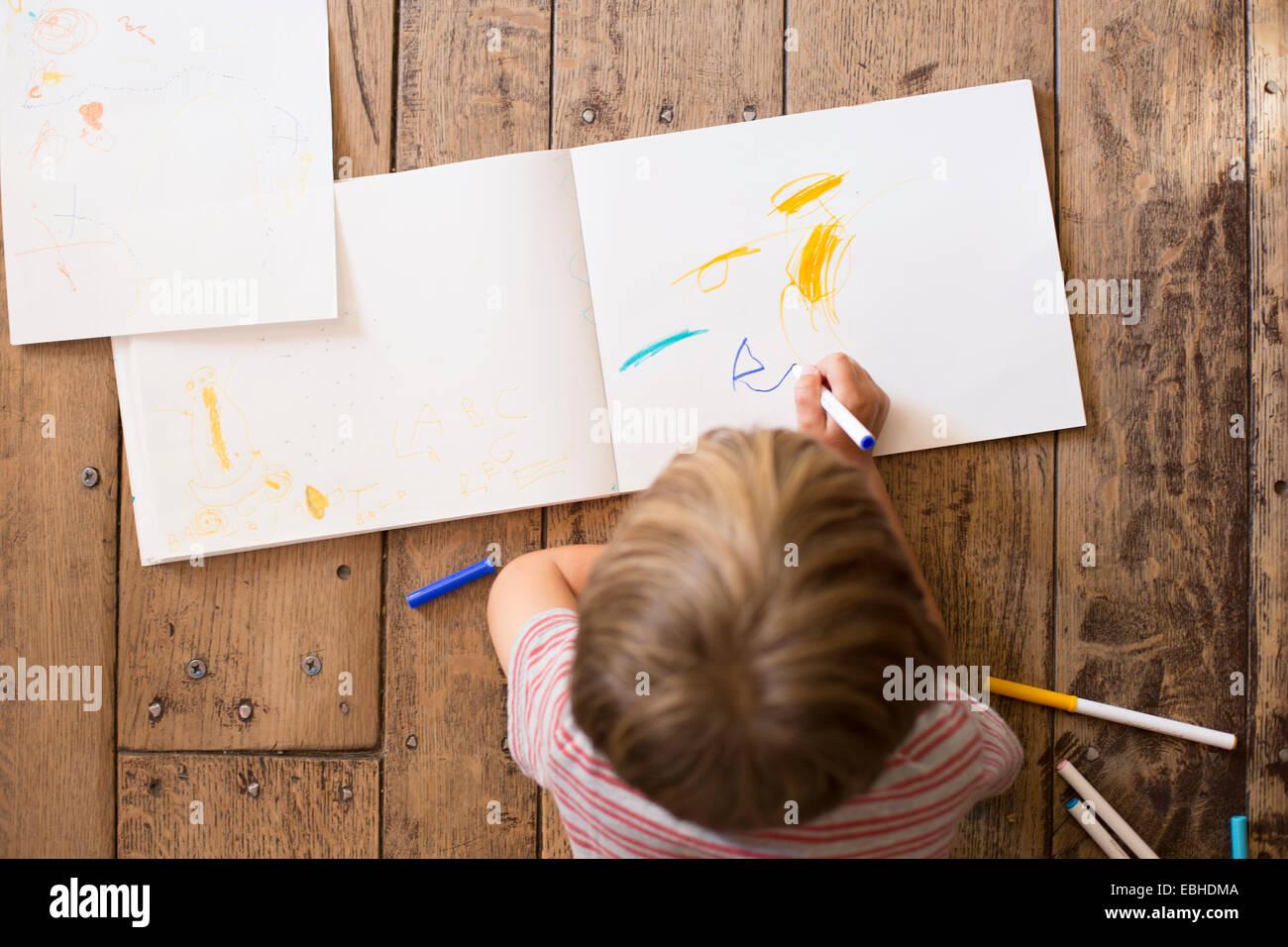 Ragazzo giovane disegno su carta, angolo alto Immagini Stock