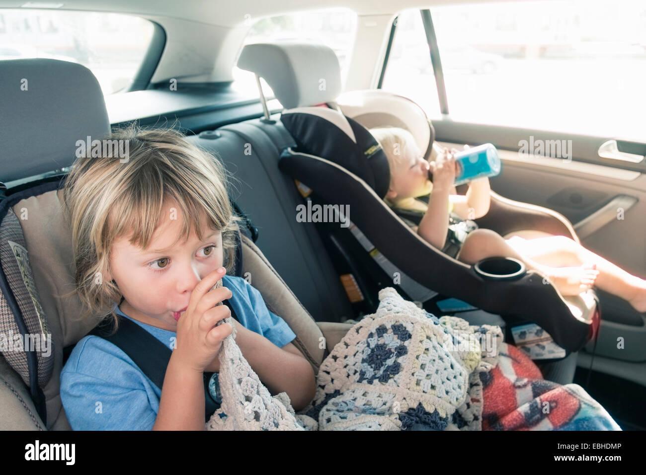 Due ragazzi in seggiolini per auto Immagini Stock