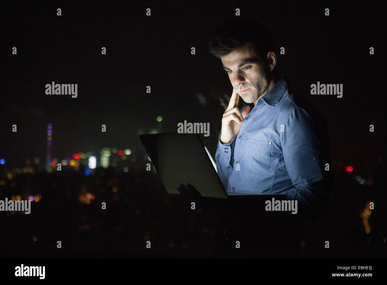 Giovane imprenditore guardando portatile nella parte anteriore del grattacielo Finestra di ufficio di notte, Shanghai, Immagini Stock