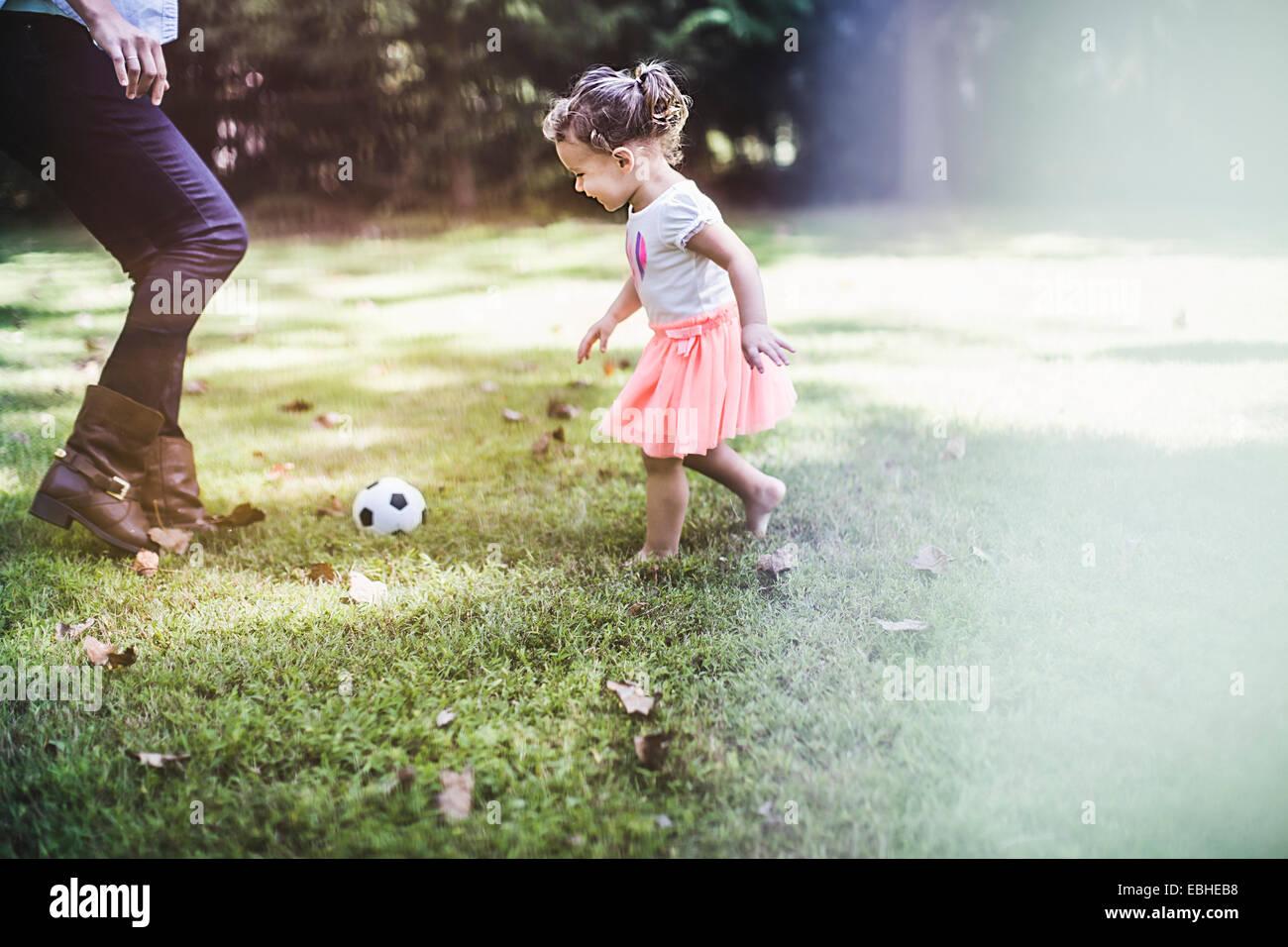 Bambina che gioca con la palla in giardino Immagini Stock