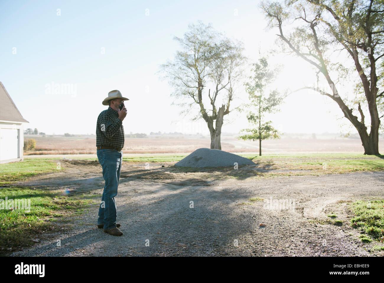 Senior agricoltore maschio chattare su smartphone su sterrato, Plattsburg, Missouri, Stati Uniti d'America Foto Stock