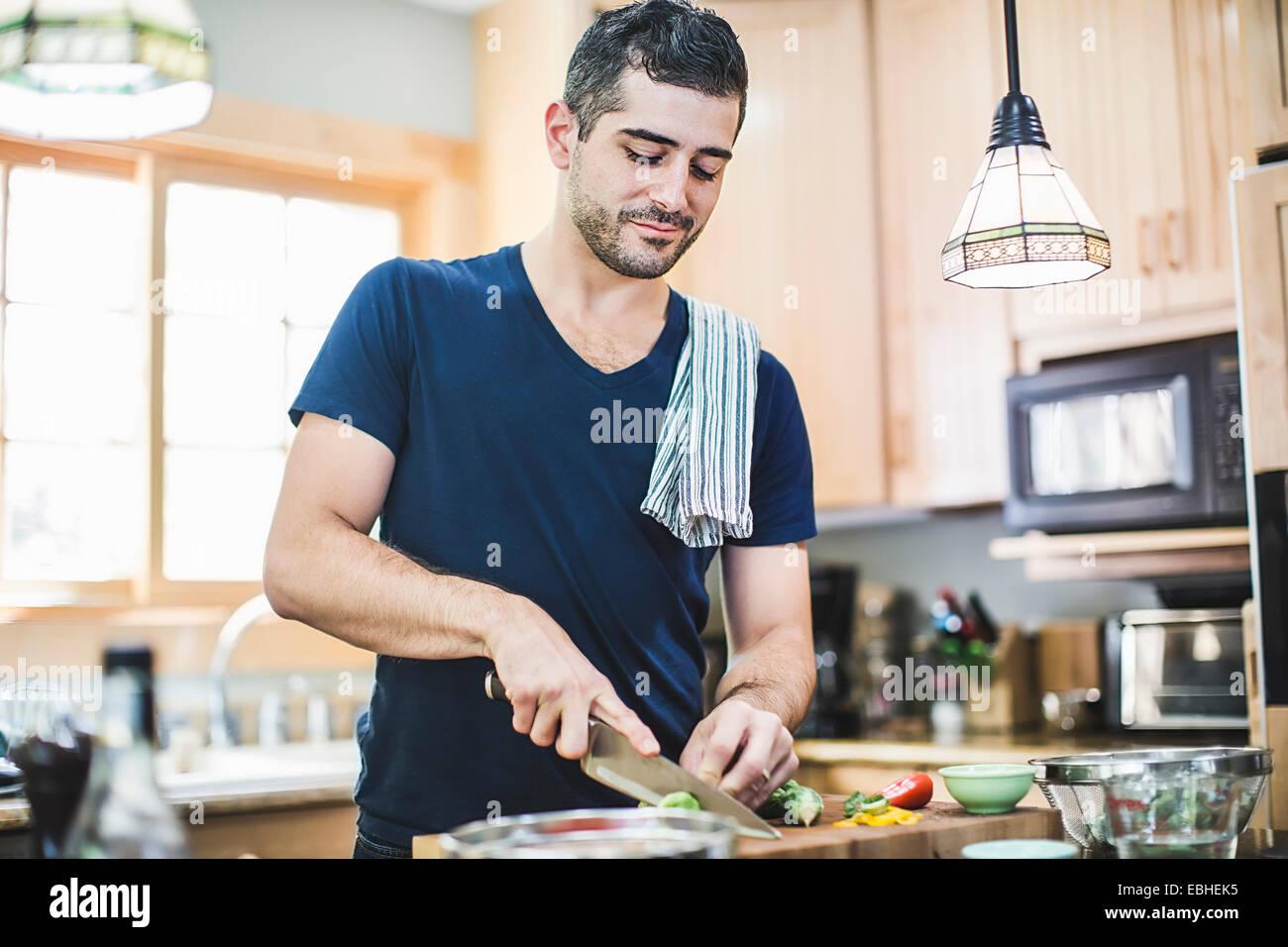 L uomo nella preparazione degli alimenti in cucina Immagini Stock