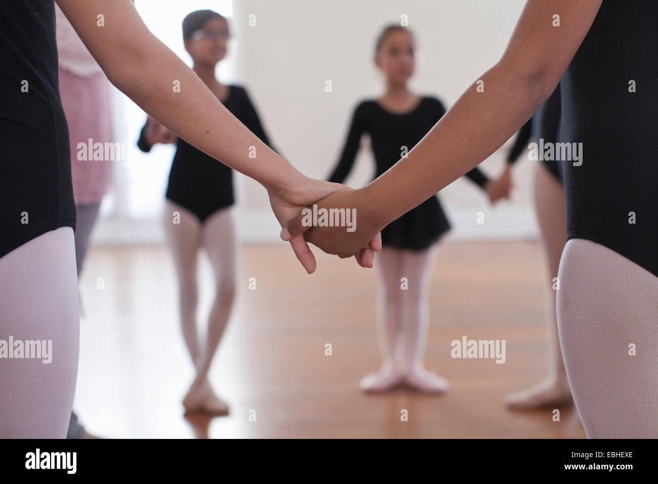 Vista posteriore di un gruppo della scuola di danza ragazze tenendo le mani Immagini Stock