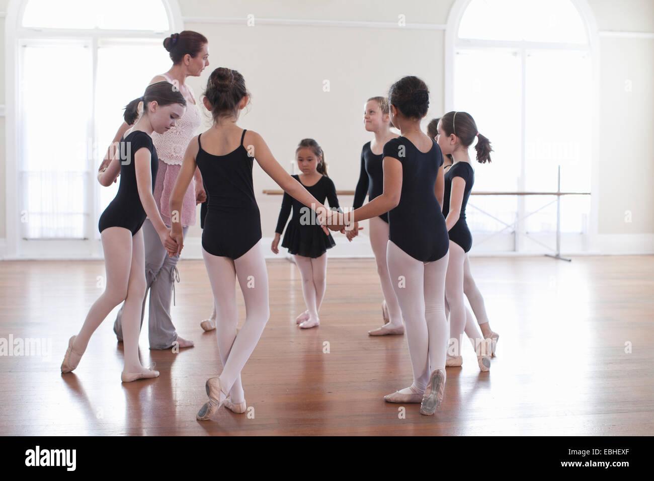Insegnante di danza tenendo le mani con il gruppo della scuola di danza ragazze Immagini Stock