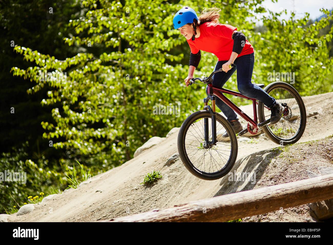 Giovani femmine bmx biker di accelerare le rocce in foresta Immagini Stock