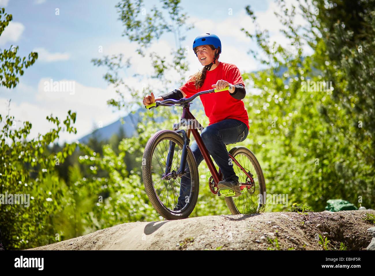 Giovani femmine bmx biker in bilico sul bordo del rock in foresta Immagini Stock