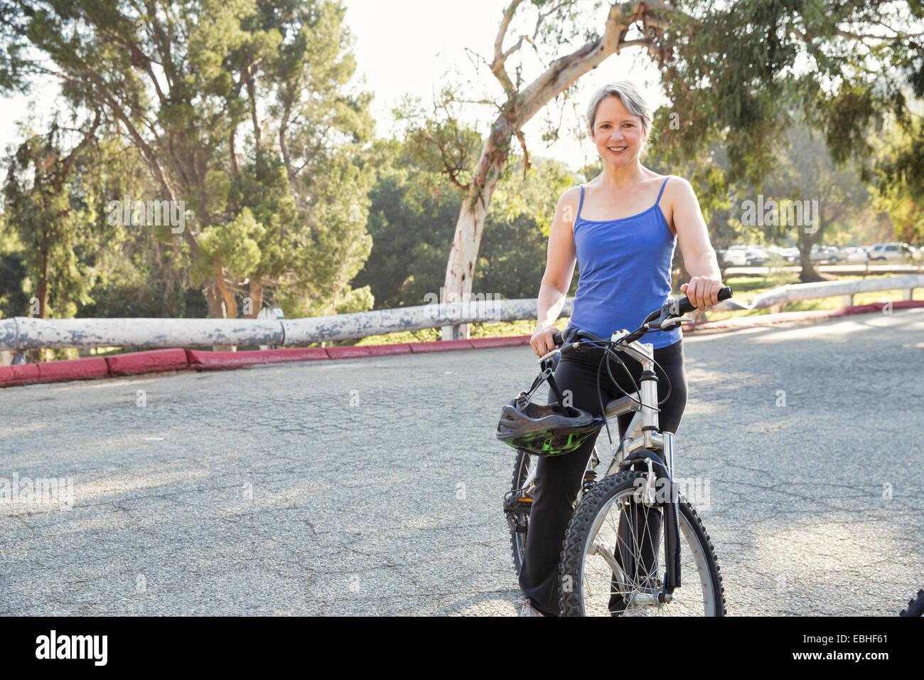 Ritratto di donna matura ciclista in posizione di parcheggio Immagini Stock