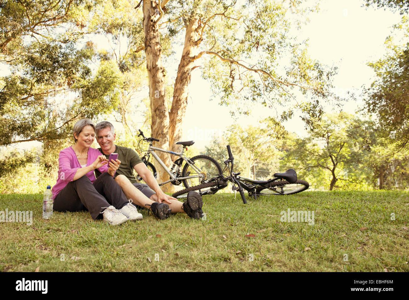 Coppia ciclismo giovane seduto in park guardando smartphone Immagini Stock