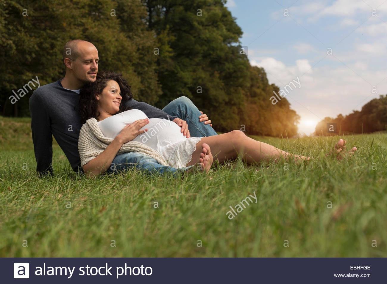 Incinta giovane seduto sull'erba in posizione di parcheggio Immagini Stock
