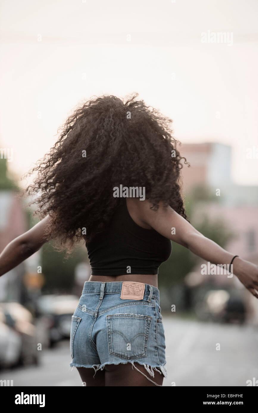 Giovane donna con i capelli neri e braccia Immagini Stock