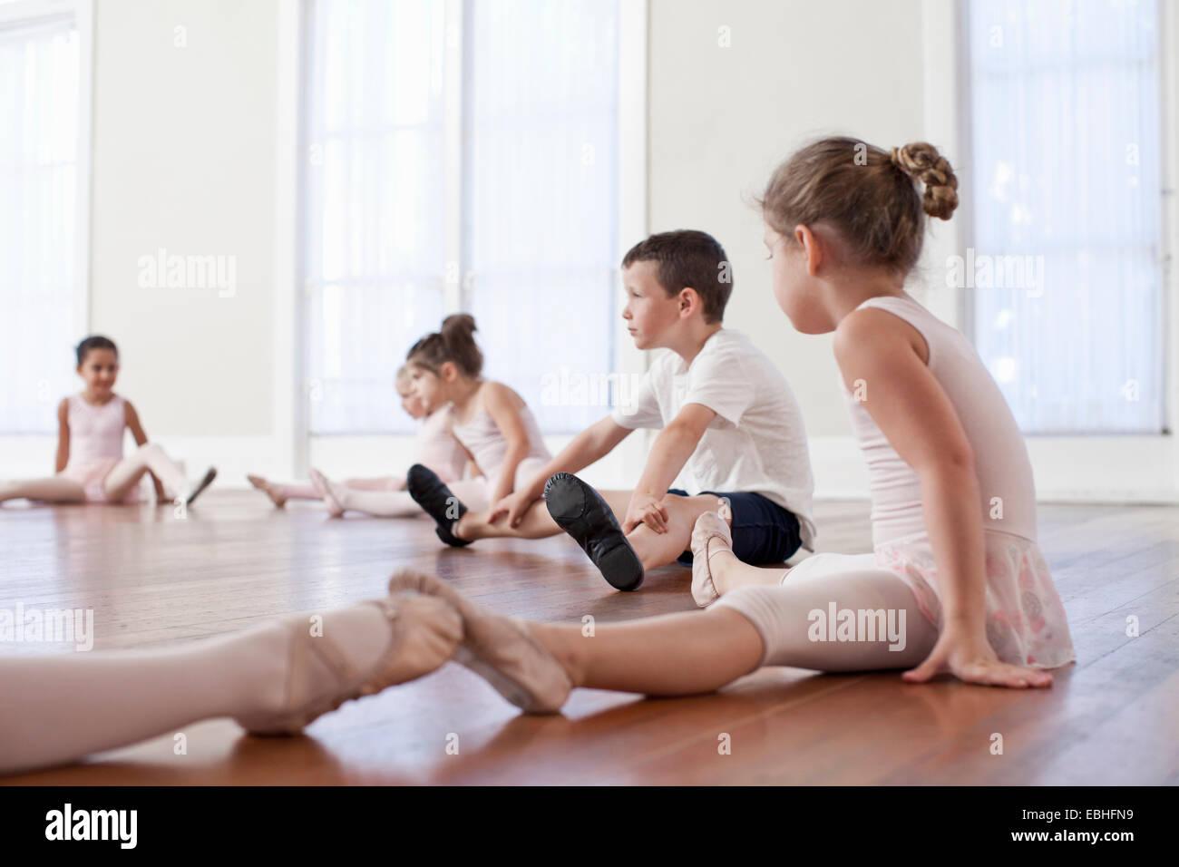 Bambini seduti sul pavimento la pratica posizione di balletto in scuola di danza Immagini Stock