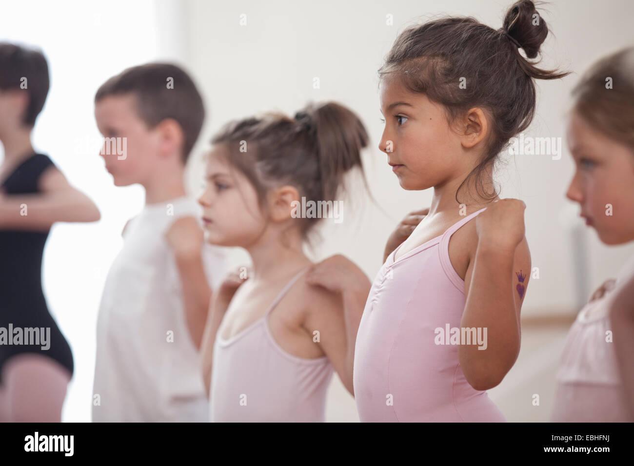 Fila di bambini praticando nella scuola di danza Immagini Stock