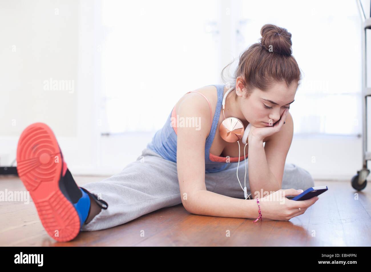 Ragazza adolescente in fase di riscaldamento e guardando smartphone nella scuola di danza Foto Stock