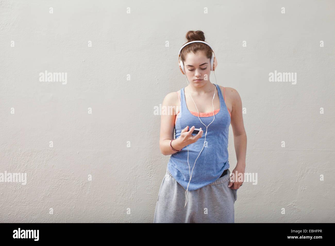 Ragazza adolescente ascoltando musica dello smartphone in scuola di danza Immagini Stock