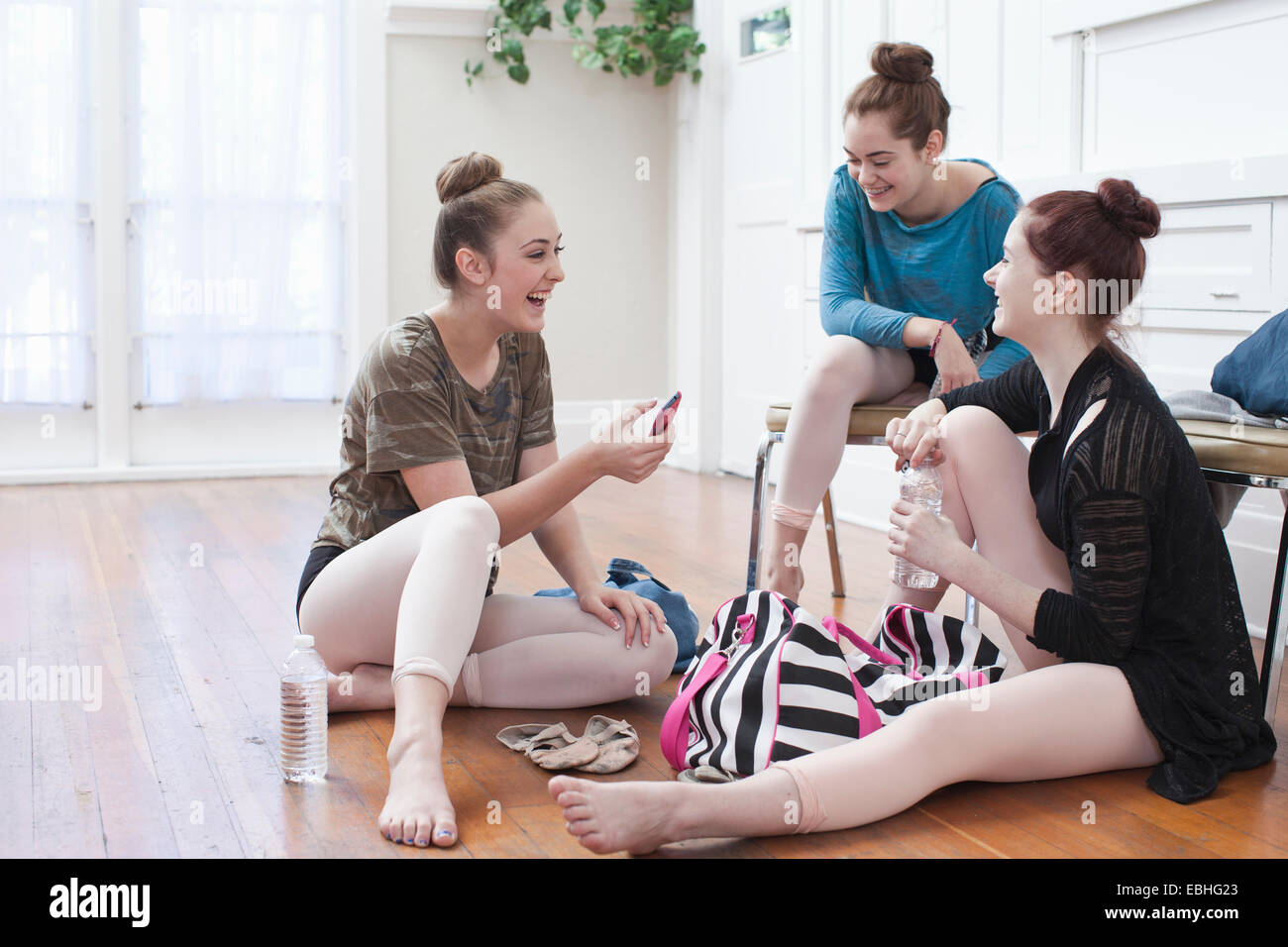 Tre ragazze adolescenti in chat e ridere in scuola di danza Immagini Stock