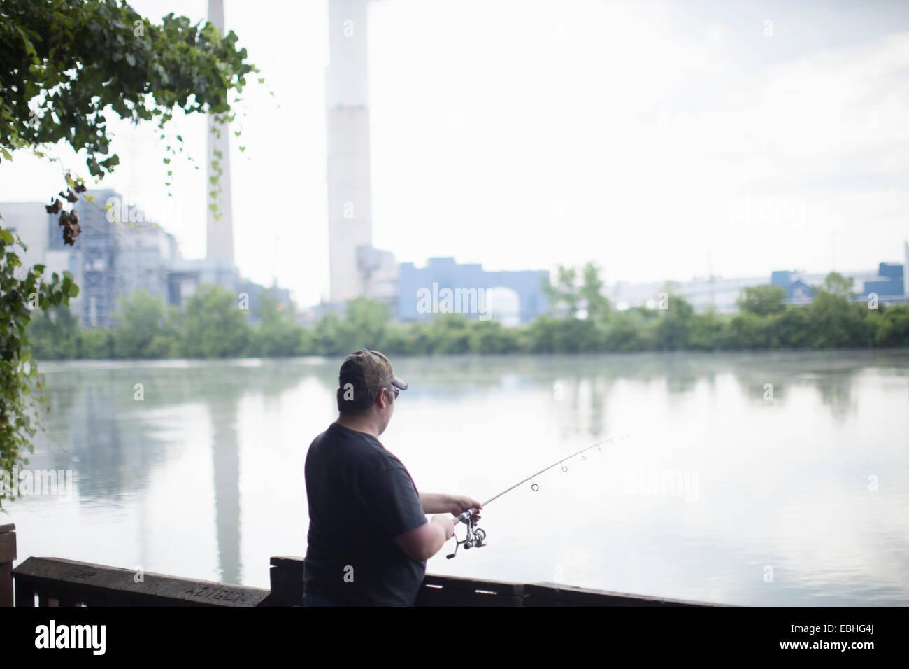 L'uomo la pesca di fronte la Detroit Edison Power Station, fiume Raisin, Monroe, Michigan, Stati Uniti d'America Foto Stock