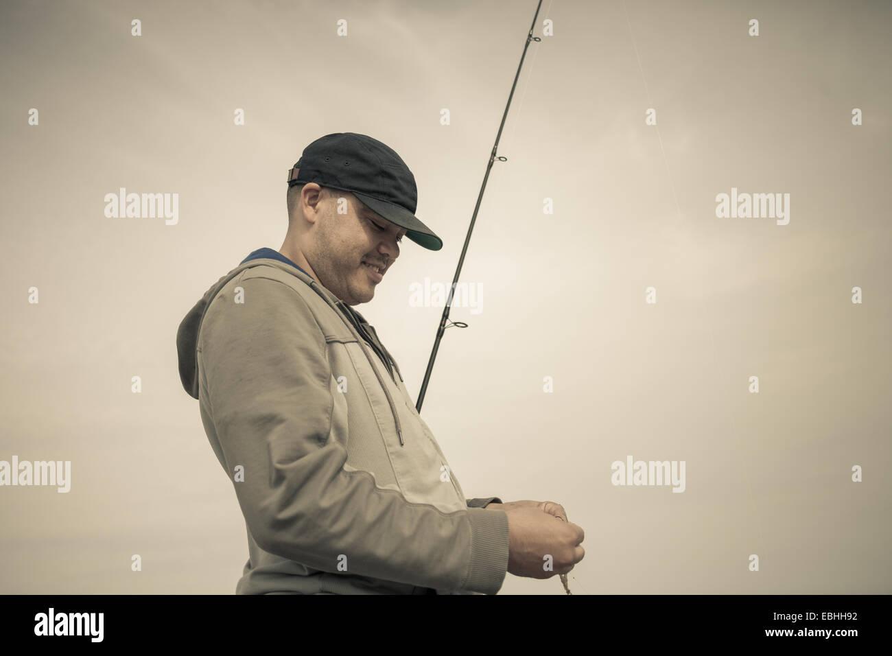 Fisherman preparazione di canna da pesca, Truro, Massachusetts, Cape Cod, STATI UNITI D'AMERICA Foto Stock