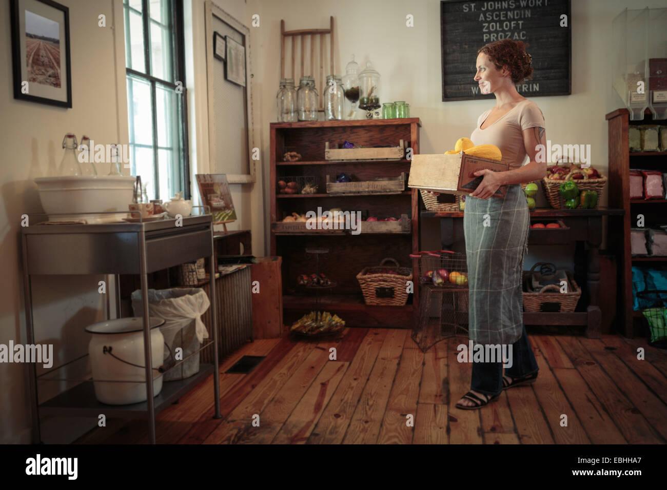 Femmina assistente shop il trasporto di frutta e verdura cassa nel paese store Foto Stock