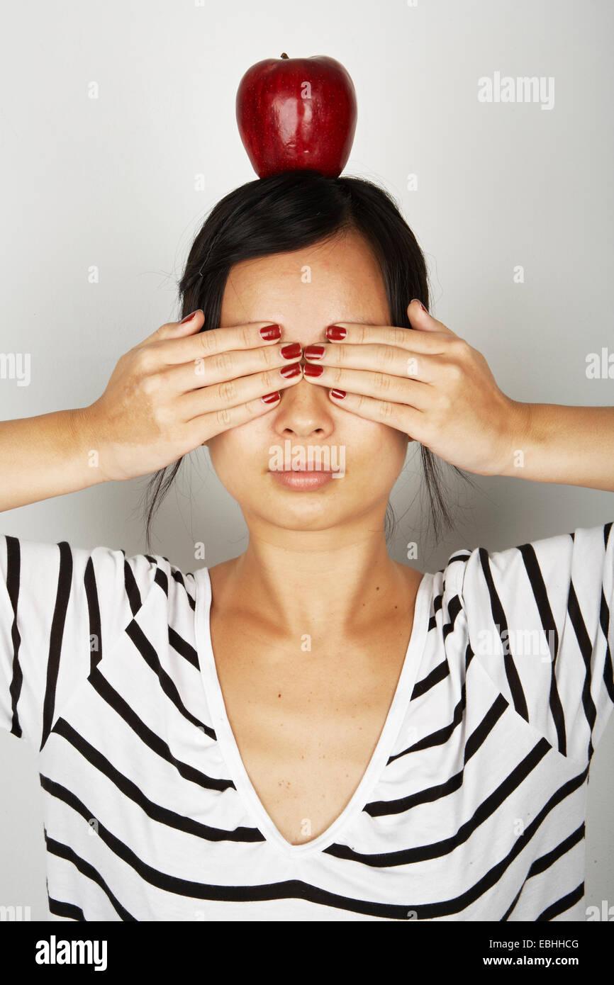 Ritratto in studio di metà donna adulta che copre gli occhi e una mela rossa sulla sua testa Immagini Stock