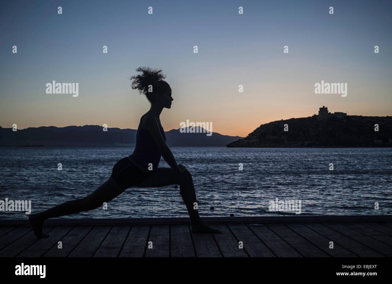 Giovane donna fare yoga per mare, silhouette Immagini Stock