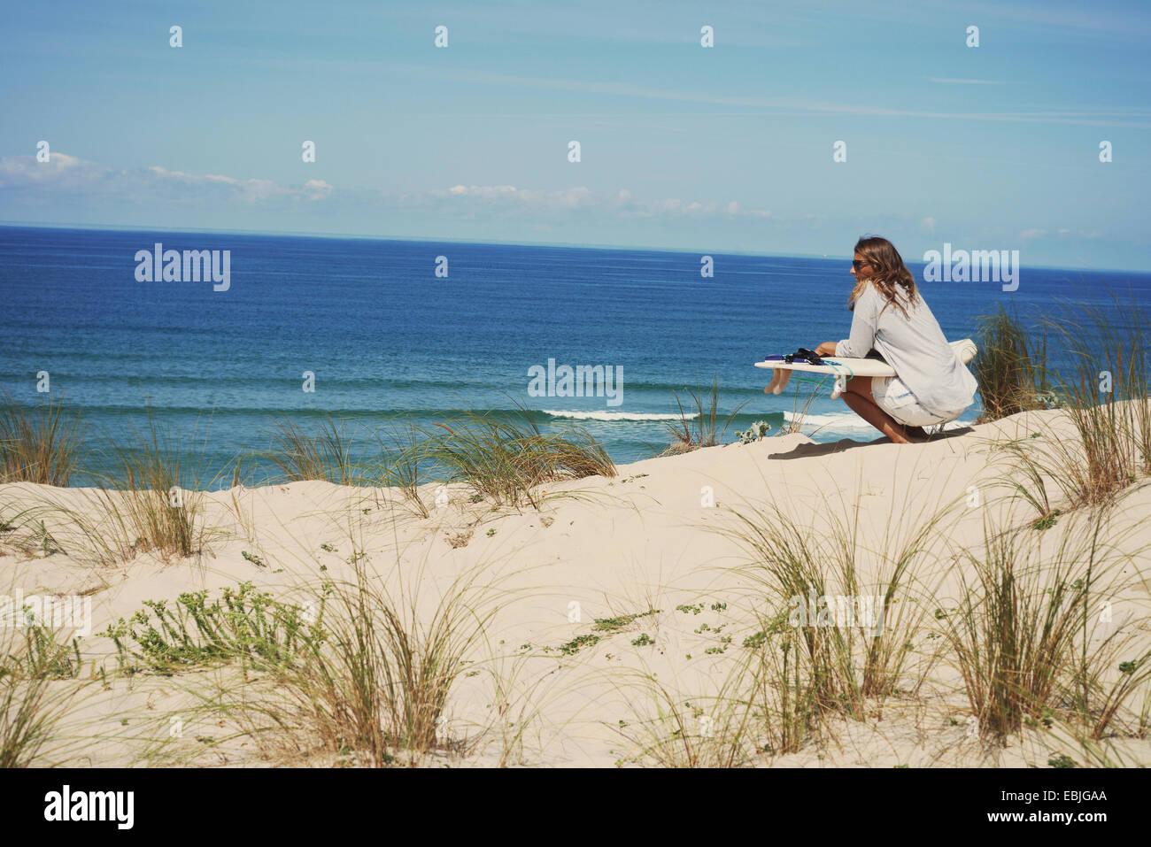 Donna con la tavola da surf sulla spiaggia Lacanau, Francia Immagini Stock