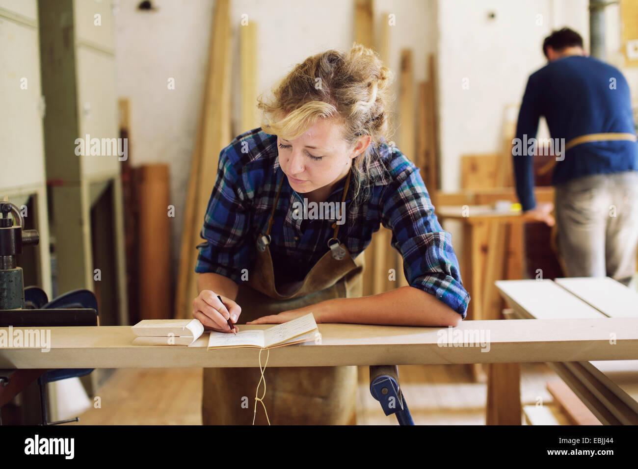 Giovani craftswoman rendendo note in organo a canne workshop Immagini Stock