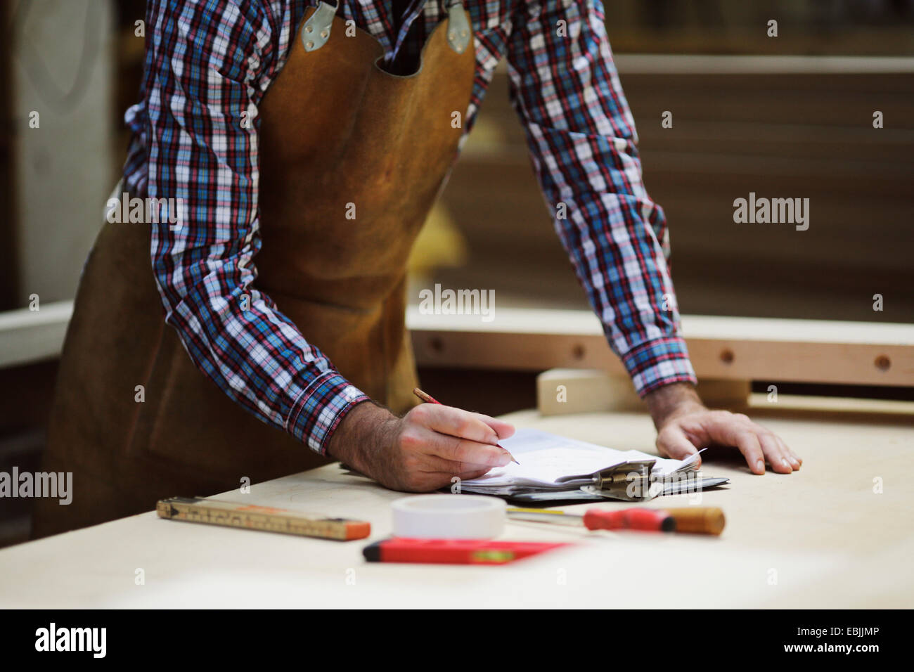 Ritagliato shot di maturo artigiano rendendo note in officina di organo Immagini Stock