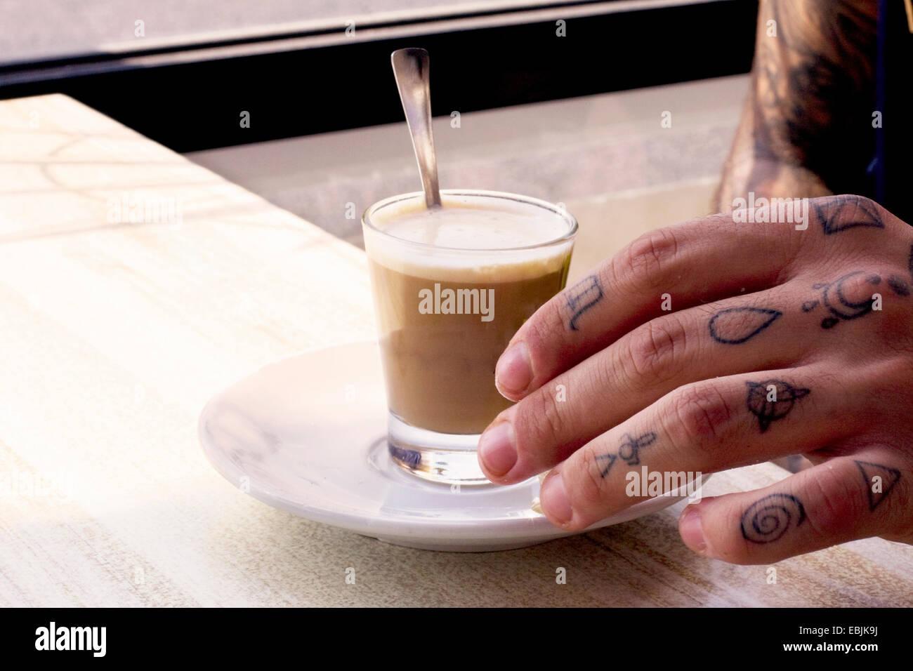 Tatuato mano del giovane uomo e caffè shotglass sul tavolo del bar
