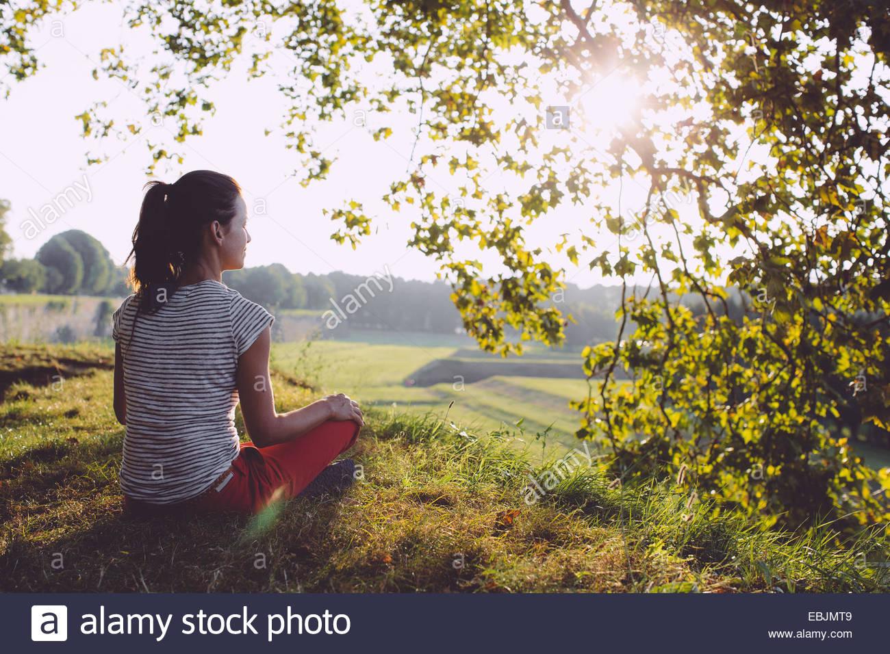 Vista posteriore della metà donna adulta seduta guardando alla vista del paesaggio, Toscana, Italia Immagini Stock