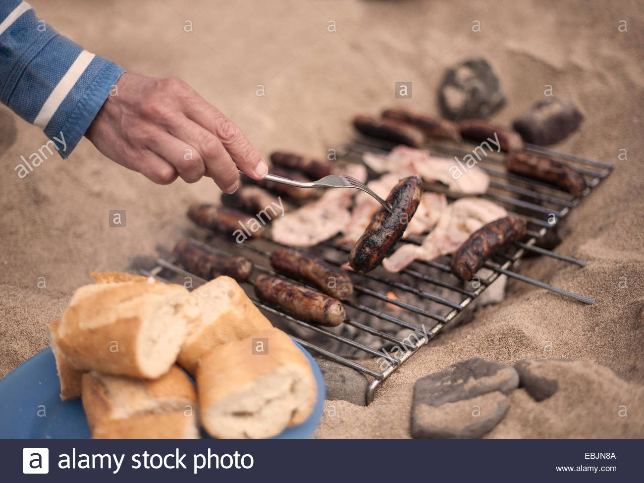 Persona alla brace salsicce Immagini Stock