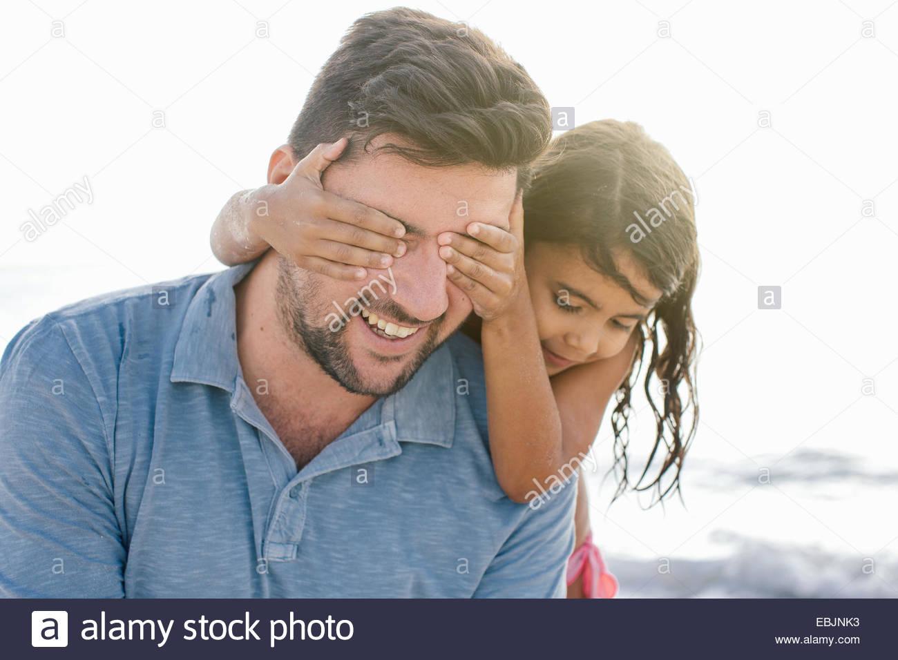 La ragazza con le mani che coprono gli occhi dei padri sulla spiaggia, Toscana, Italia Immagini Stock