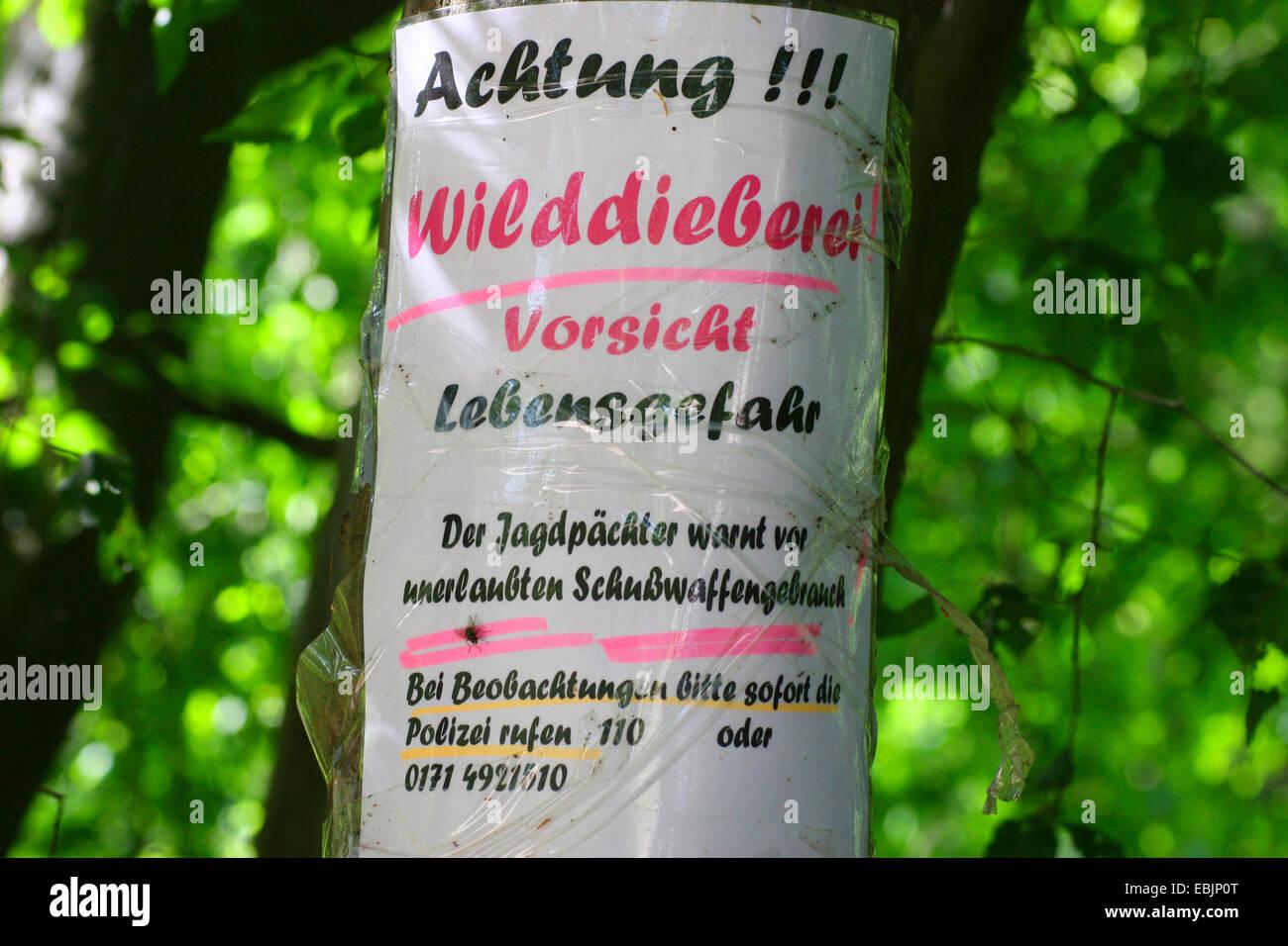 Segno di un albero in guardia contro i pericoli del bracconaggio nella zona, Germania Immagini Stock