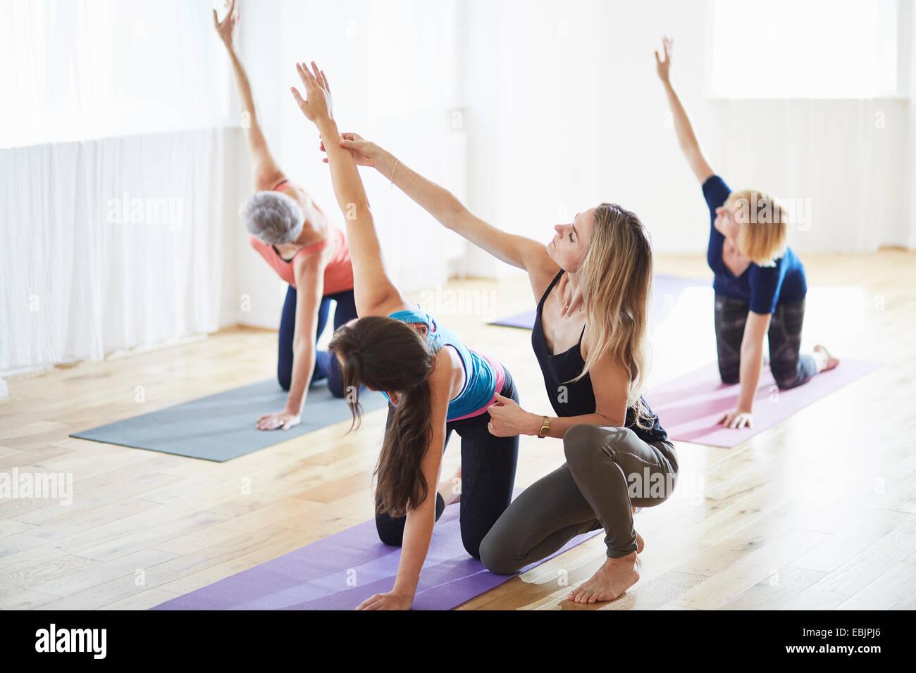 Le donne inginocchiandosi e i bracci di sollevamento nella classe di pilates Immagini Stock