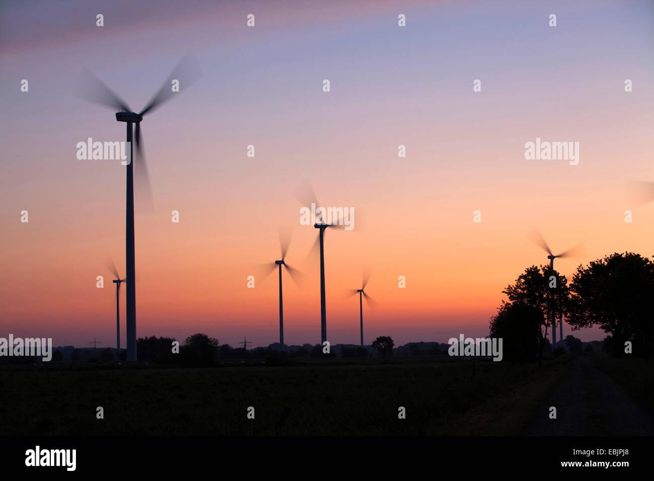 Sagome di un impianto di energia eolica a sunrise, Germania Immagini Stock