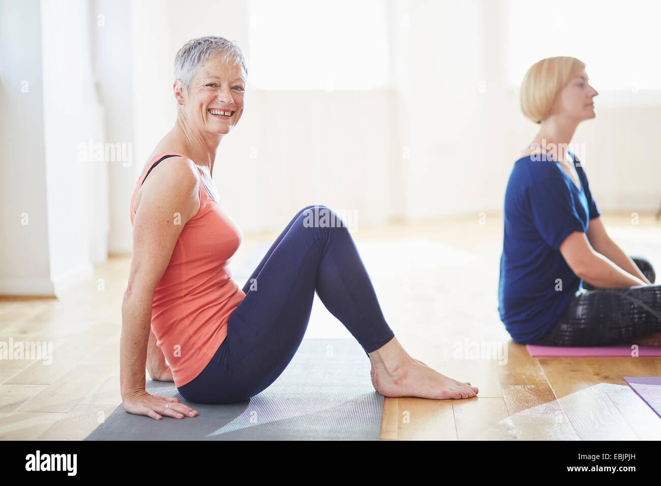 Ritratto di donna matura seduta sul pavimento nella classe di pilates Immagini Stock