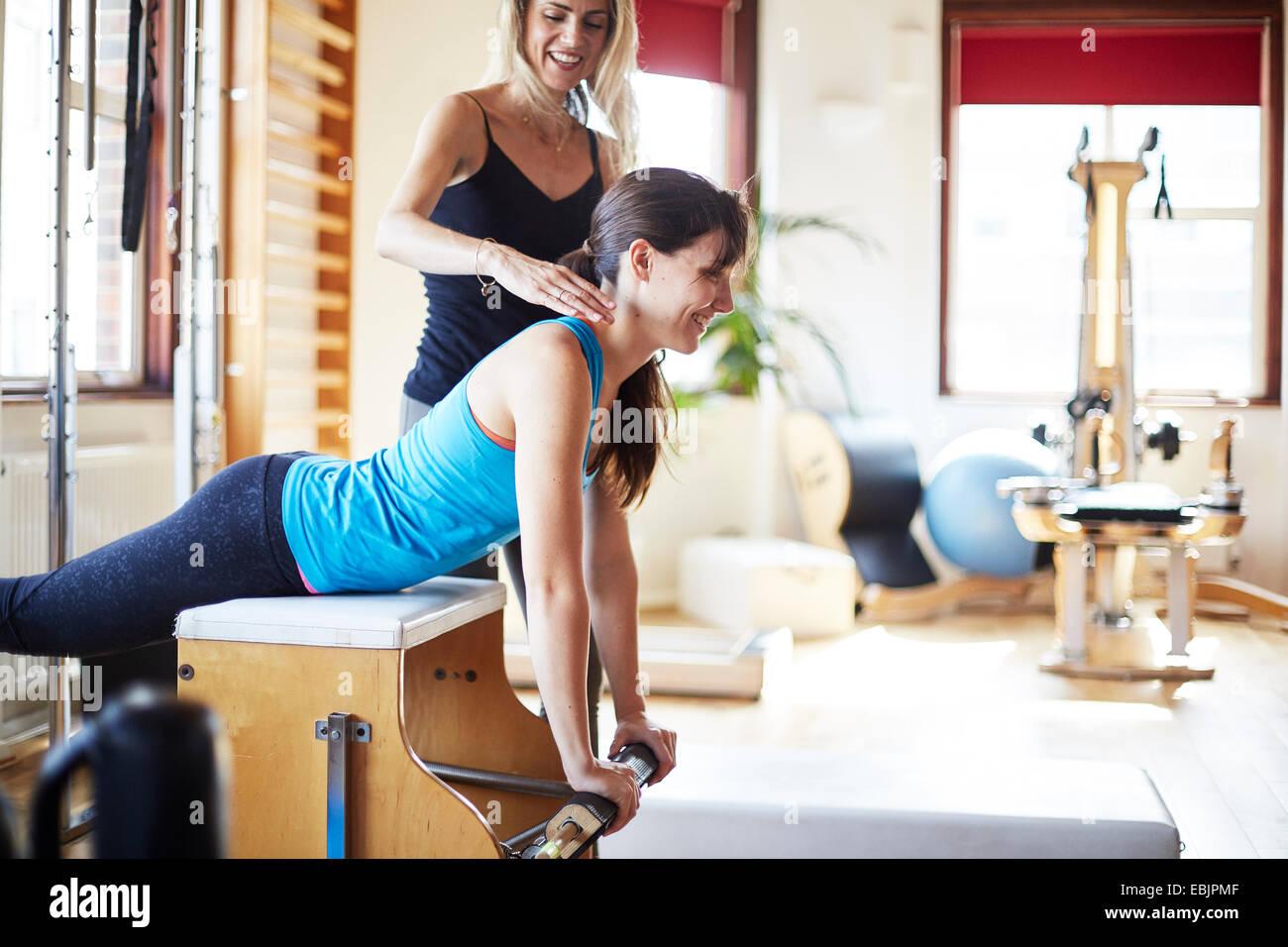 Giovane studentessa spingendo verso l'alto dal combo chair in palestra pilates Foto Stock