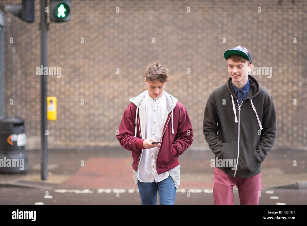 Due amici maschi strada di attraversamento Foto Stock