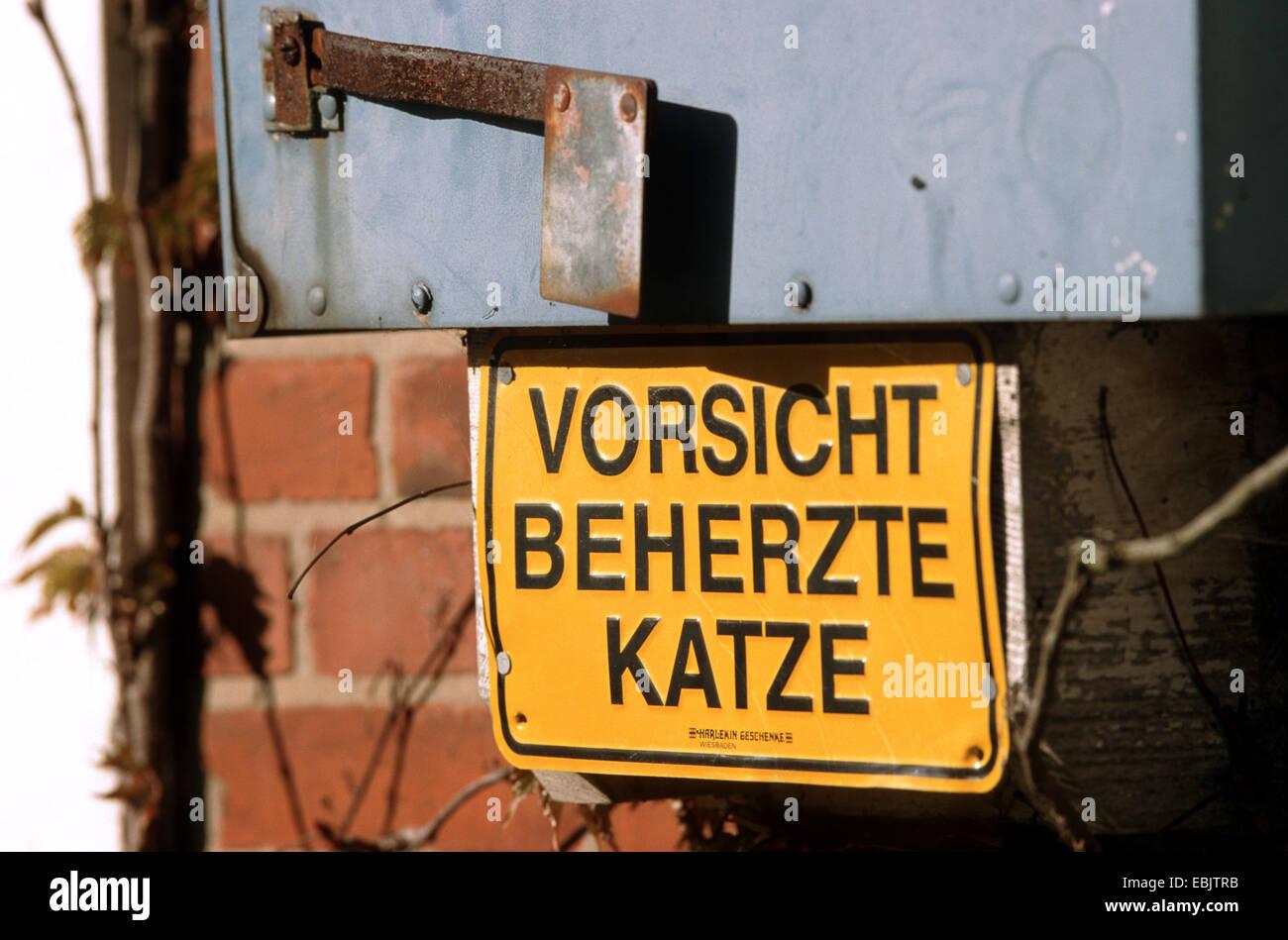 """Cartello che diceva """"Vorsicht beherzte Katze' ('attenzione, coraggioso cat') all'ingresso di una proprietà Foto Stock"""