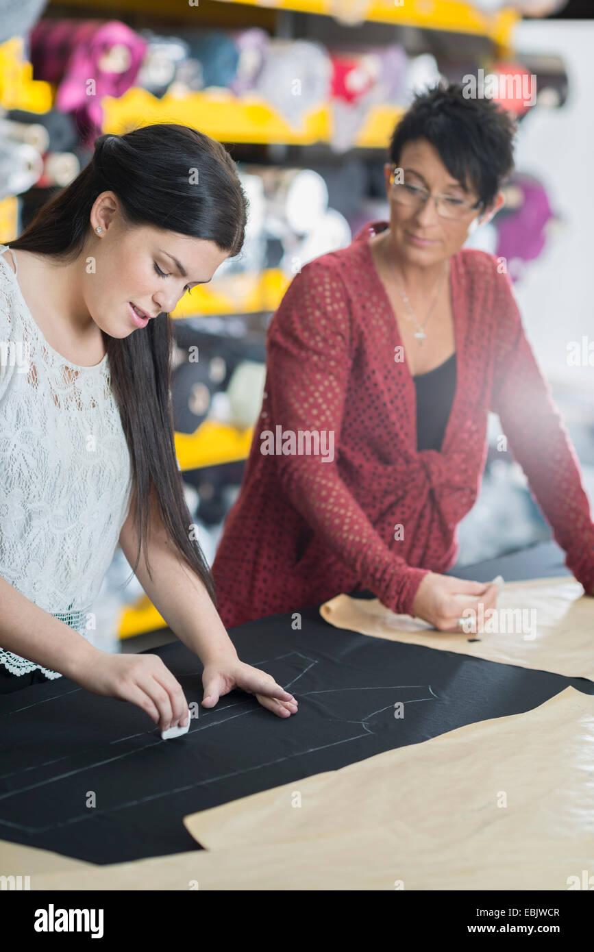 Due seamstresses sfarinamento delineano su prodotti tessili sul tavolo di lavoro Immagini Stock