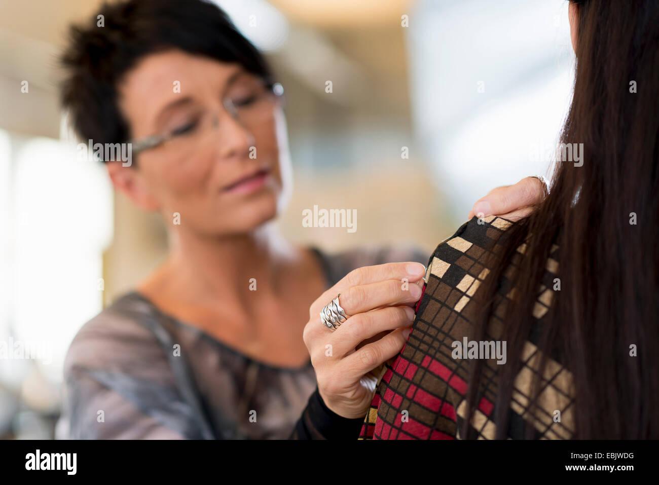 Coppia sarta pinning spalla di clienti abito in officina Immagini Stock