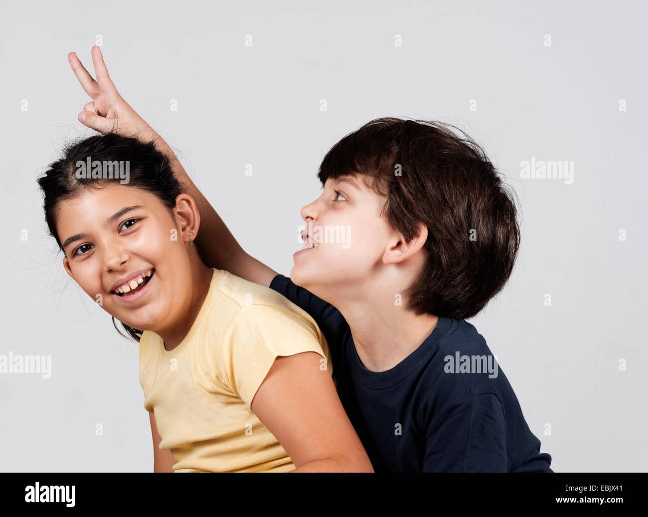 Ragazzo e ragazza giocando, ragazzo giovane azienda fino le dita come orecchie di coniglio Immagini Stock