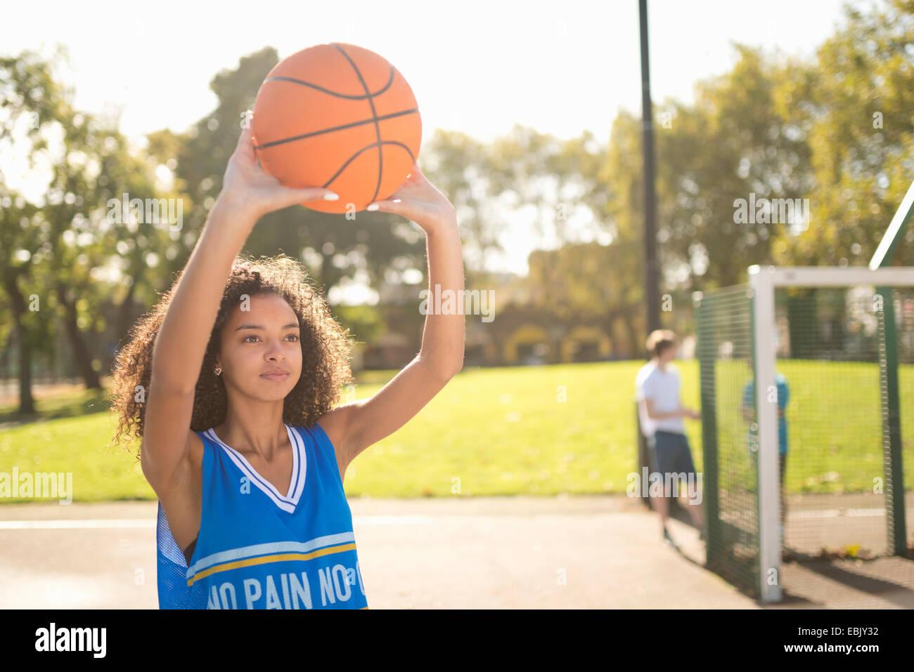 Femmina giovane giocatore di basket tenendo in mano la pallacanestro Immagini Stock