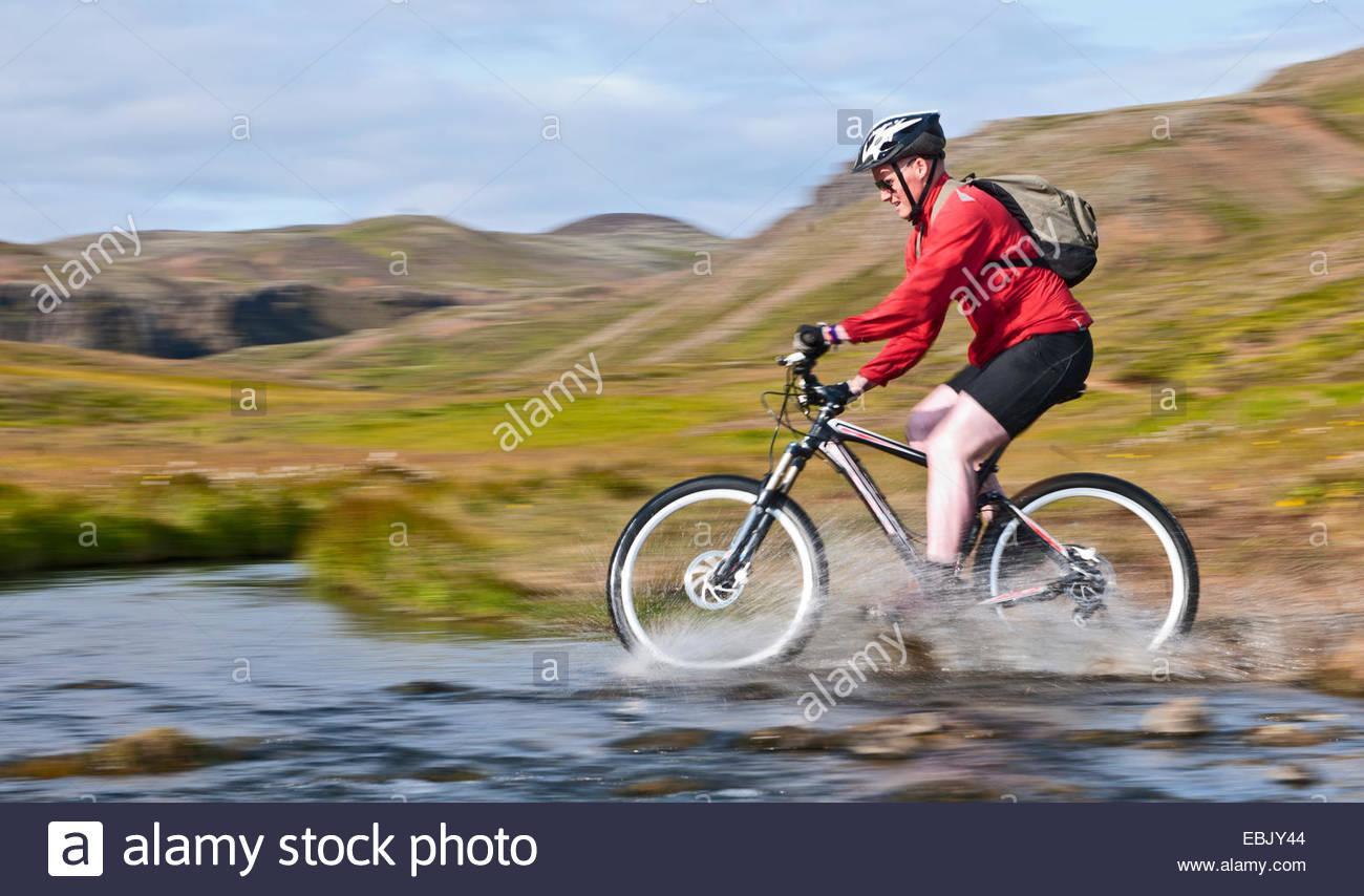 Giovane maschio mountain biker ciclismo di velocità attraverso il fiume caldo, Reykjadalur Valley, nel sud Immagini Stock