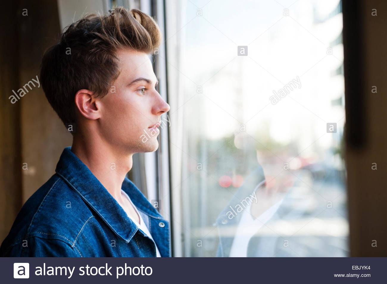 Giovane uomo guardando attraverso la finestra cafe Immagini Stock