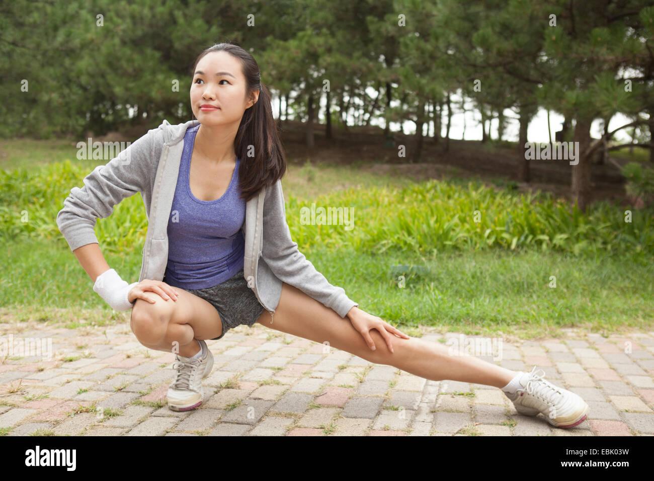 Giovani femmine runner stretching gambe in posizione di parcheggio Immagini Stock