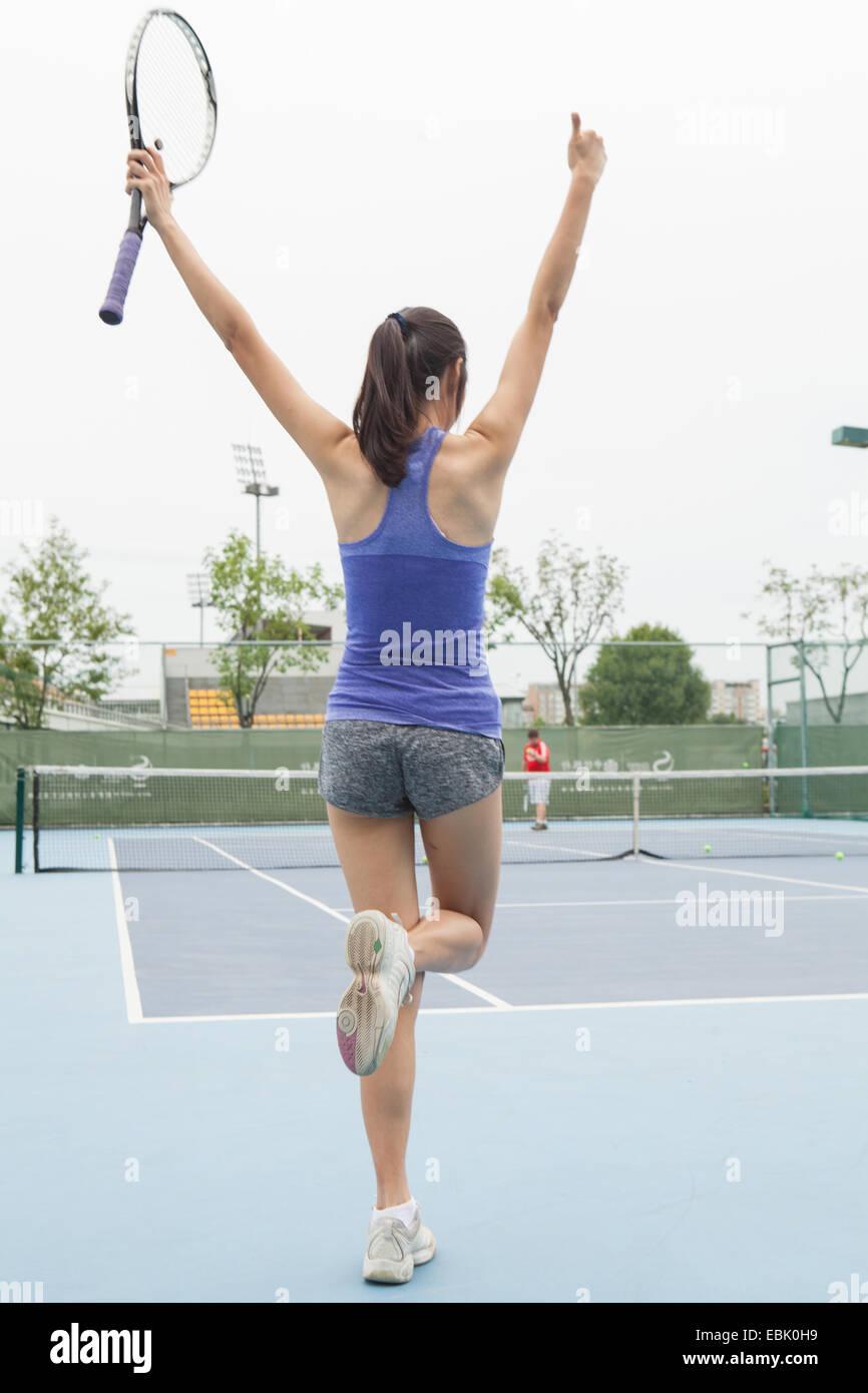 Vista posteriore della femmina giovane giocatore di tennis celebra sul campo da tennis Immagini Stock