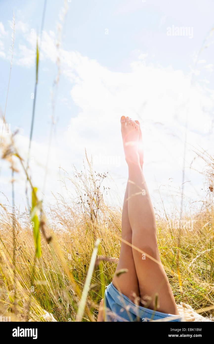 Giovani womans gambe nude in un campo di erba lunga Immagini Stock