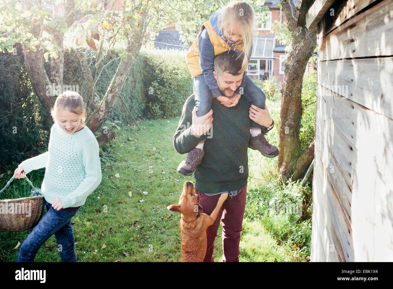 Padre con la figlia sulle spalle in giardino Immagini Stock