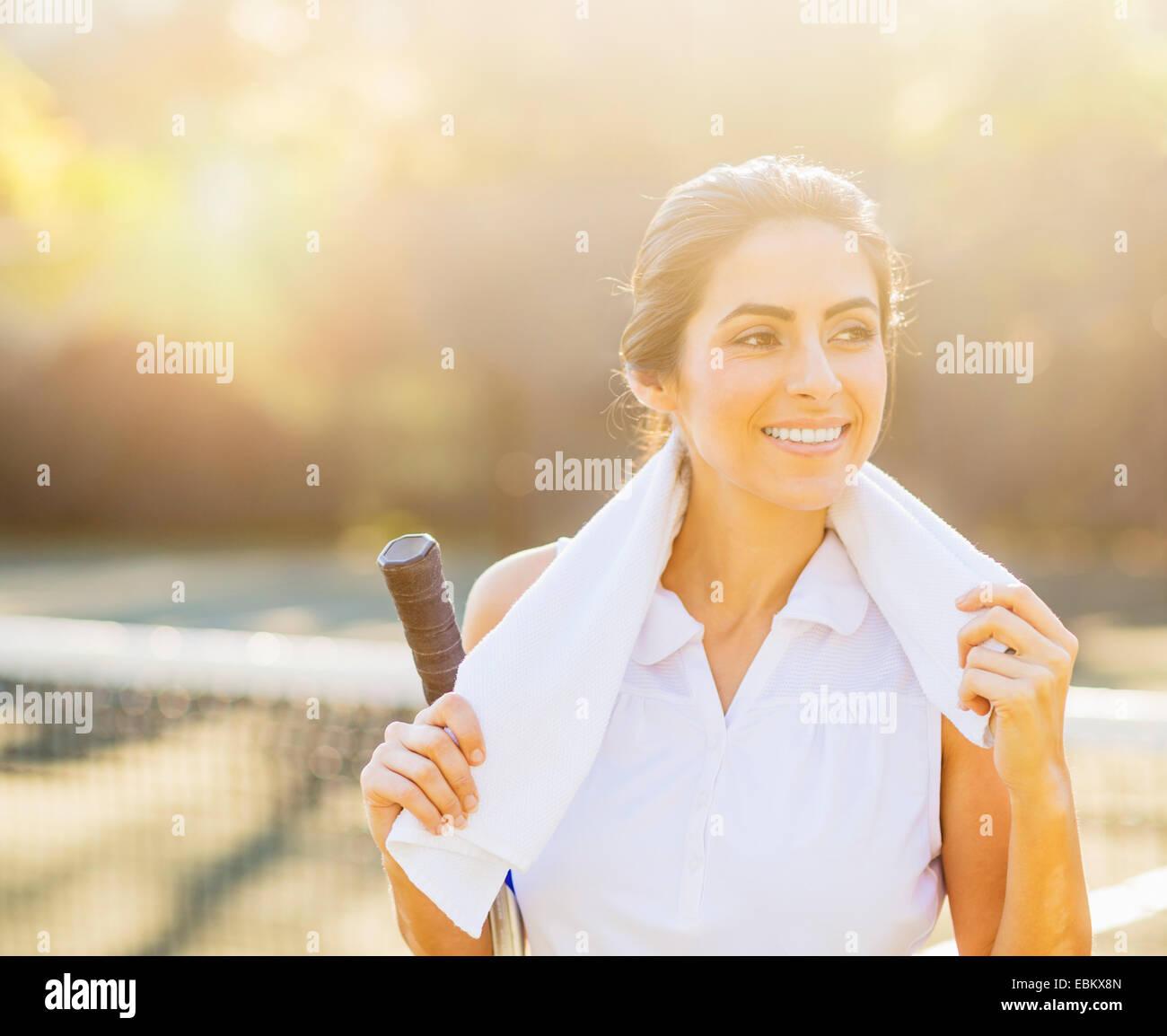 Ritratto di sorridente giovane donna con asciugamano e racchetta da tennis Immagini Stock