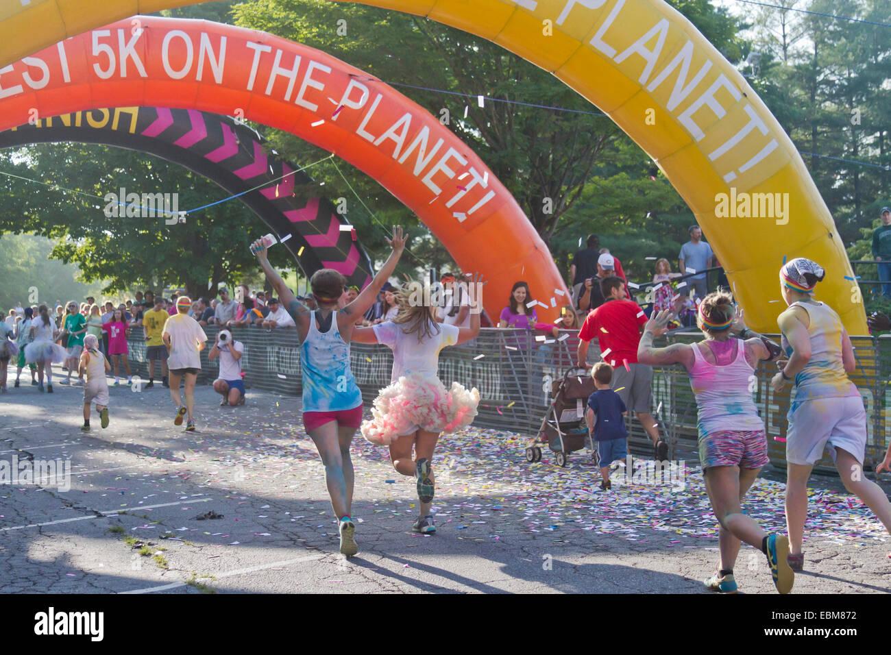 Felice opener guide con coloranti colorati si avvicinano al traguardo in Asheville 5K COLOUR RUN Immagini Stock